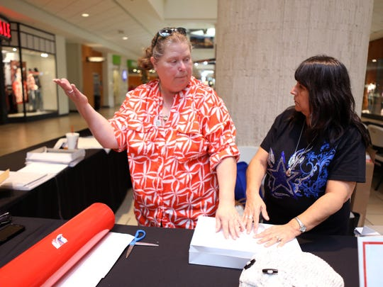 Charlene Scott, community relations specialist from the Deaf & Hard of Hearing Center, and Nina Cervantes, a member of the silver silent senior citizen group, wrap gifts at La Palmera mall on Friday, December 1, 2017. Through the end of the month a variety of nonprofits will be wrapping gifts at the mall for a donation.