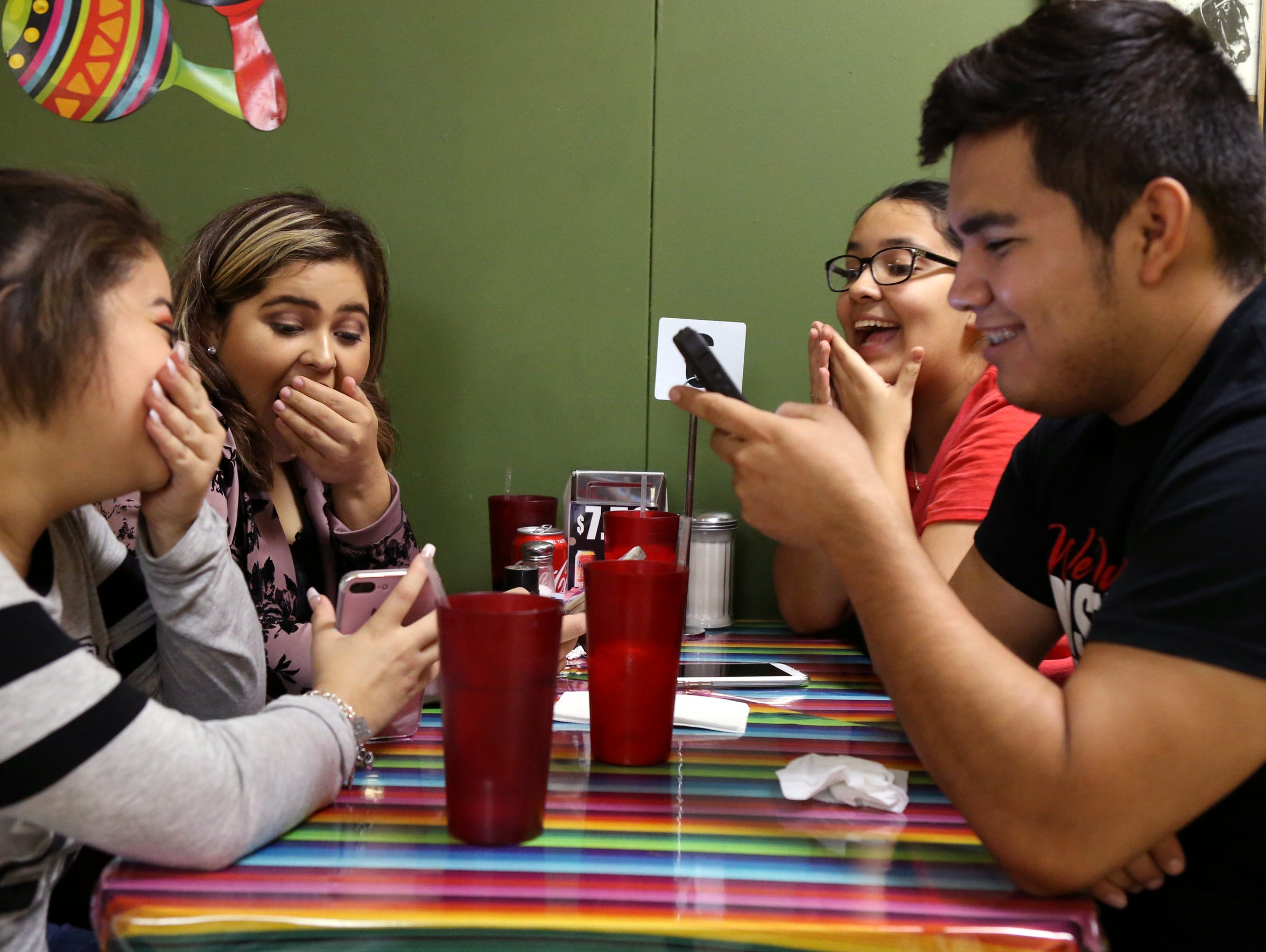 """Karen Barrera, 19, (clockwise from left), Claudia Jimenez, 19, Erica Jimenez, 17, and Sergio Alfaro, 19, hang out at To-Ce-Chi following the Ray High School homecoming Parade on October 23, 2017. """"I know I'm Mexican, and I know I live here, so sometimes I do feel like, I'm already here, I'm already a citizen,"""" Claudia said. """"But then, sometimes they remind you, no you're not a citizen, you're Mexican, you're an illegal Mexican. """""""