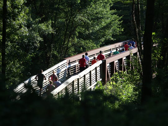 Runners participate in the Leftovers Prediction Run Thursday night at Lake Conestee Nature Park.