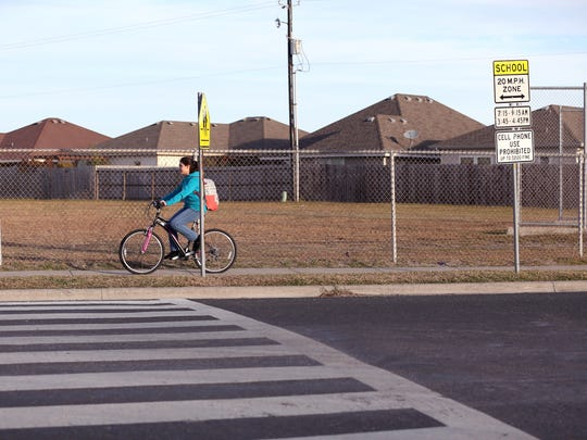 A Grant Middle School student rides her bike to school along Aaron Drive on January 23, 2018. When the Corpus Christi Independent School District instituted later end times this year, the city, along with the district, decided not to change school zone signage due to the cost of replacing the signs, the intention of CCISD in seeking a District of Innovation status and the time it would have taken to replace and reprogram the nearly 1,000 plaques and 149 flashing signs before school started.