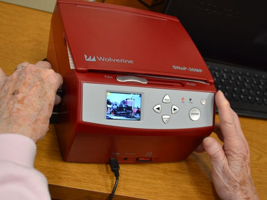 Doris Libben views a photo from a slide in the Wolverine Photo Digitizer. The equipment digitizes the photos, which can then be stored on a thumbdrive or SD card. The photo digitizer is available for use until Feb. 23.