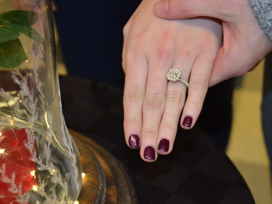 "Kayla Schmitt shows off the ring, next to the ""enchanted flower"" box it came in."