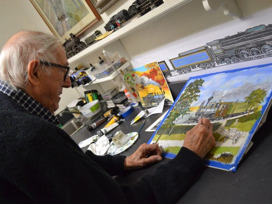 Bob Lorenz works on his latest train painting in his