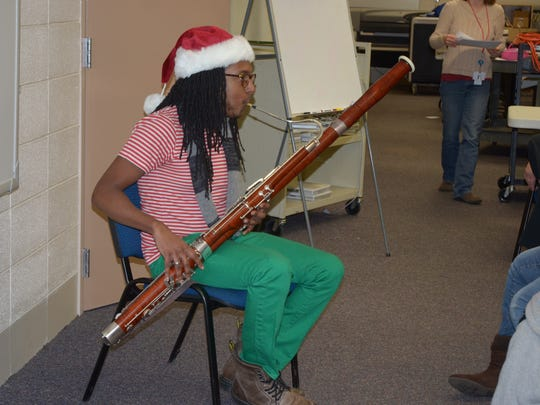 """Garrett McQueen is game for anything that helps kids listen to music. Here, he's """"Elf Garrett"""" at Christmastime in 2014, playing for students at Sarah Moore Greene."""