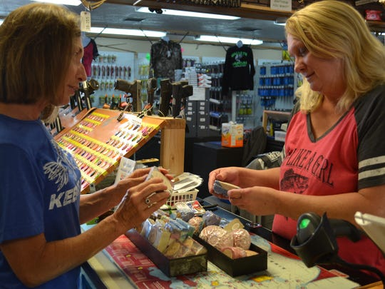 Soni Fashner, left, talks about her bath and body line with Patty Coons at Happy Hooker Outdoors. Coons brought the product line to the store in an effort to offer more options to her many female customers.