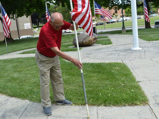 Larry Cronin places a flag at Flag Park near the Sandusky