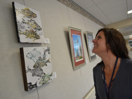 Elisabeth Brand enjoys the work of artist Kay Young on Magruder Hospital's Healing Wall. Young's work is part of the current display featuring works by members of the Port Clinton Artists' Club.