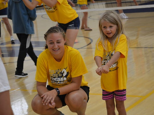 Lucy Fulweber practices newly-learned volleyball skills at Camp Wildcat on Wednesday. with the assistance of camp counselor, Katie Brugger.