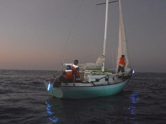 In this Tuesday, Dec. 9, 2014 photo provided by the U.S. Coast Guard, mariner Ron Ingraham and his 25-foot sailing vessel are towed to Molokai, Hawaii, after spending 12 days lost at sea.