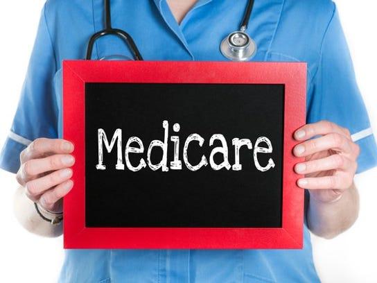 "Nurse holding chalkboard with ""Medicare"" on it."