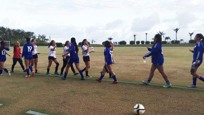 The Notre Dame Royals and George Washington Geckos line up for a round of high-fives after their IIAAG Girls' Soccer league match. The Royals won 4-0.
