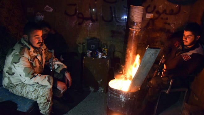 Syrian government troops sit around a fire in Aleppo, Syria, on Dec. 29.