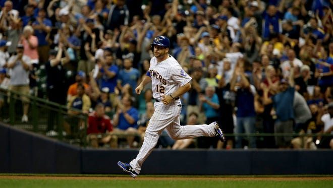 Brewers catcher Stephen Vogt circles the bases as the Miller Park faithful roar their approval in the seventh inning against the Marlins on Friday night.
