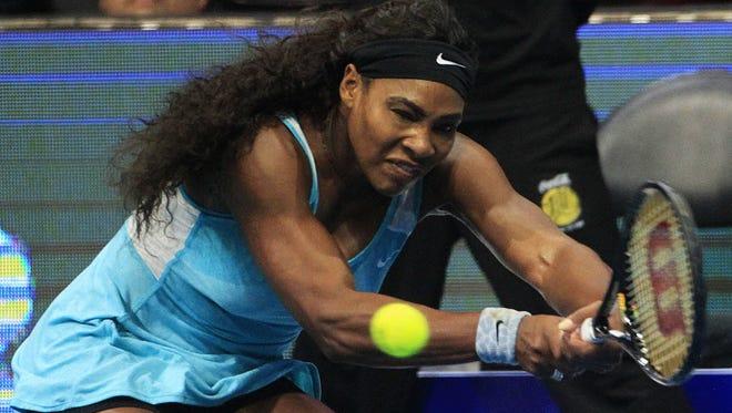 Serena Williams of the Singapore Slammers returns a shot to Kirsten Flipkens of the Manila Mavericks during their women's single match at the International Premier Tennis League (IPTL) in Manila on Nov. 30, 2014.