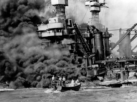 As heavy smoke rolls out of the stricken USS West Virginia, a small boat rescues a crew member from the water after the Japanese bombing of Pearl Harbor, Hawaii, Dec. 7, 1941 during World War II.  Two men can be seen on the superstructure, upper center.  The mast of the USS Tennessee is beyond the burning West Virginia.  (AP Photo)
