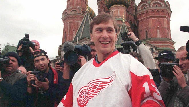 Surrounded by media, Vyacheslav Kozlov of the champion Red Wings, holds the Stanley Cup in front of St. Basil's Cathedral on Moscow's Red Square on Aug. 17, 1997. Kozlov and his teammates brought the Cup to Moscow for a four-day tour of Russia.