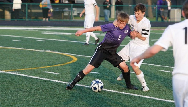 Johnston's Cade Wegner, left, battles for the ball with Ankeny Centennial's Garrett Culligan during Thursday's game at Ankeny. The Dragons posted a 2-1 overtime victory in a matchup of the top two teams in Class 3-A.