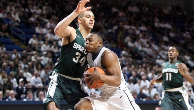 Penn State Nittany Lions guard Devin Foster (3) drives to the basket as Michigan State Spartans forward Gavin Schilling (34) defends during the first half Sunday.