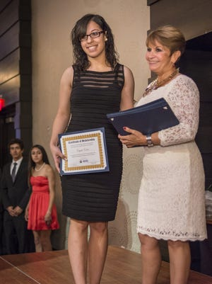 Ibero Hispanic Scholarship Endowment Fund recipient Crystal Colon accepts her award from Hilda Escher, Ibero president and CEO, at the group's 2013 annual Gala and Hispanic Scholarship Recognition Awards.