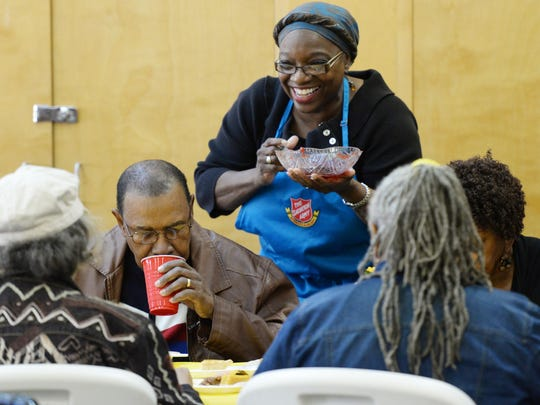Naomi Lawler serves with a smile during the Salvation Army's Thanksgiving meal for senior citizens.