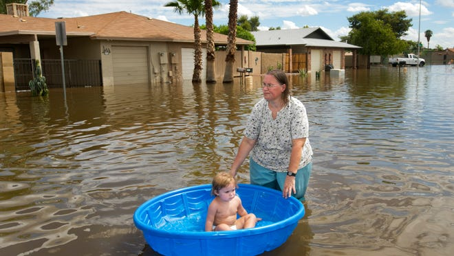 Laura Moravek carries her granddaughter, Alyssa Guarino, in a pool as they walk through the flooded road of South Allen, just east of Stapley Drive in Mesa on Tuesday, September 9, 2014.