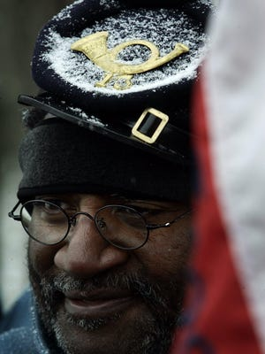 Re-enactor George Smith holds an American flag in the snow during the United States Colored Troops memorial dedication at Nashville National Cemetery in Madison on Feb. 18, 2006.