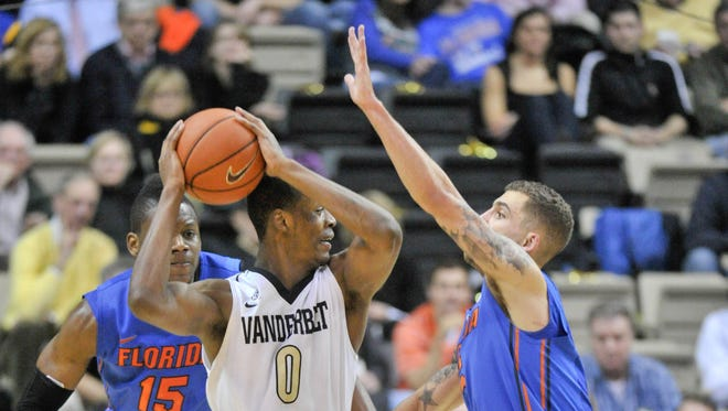Vanderbilt Commodores Rod Odom (0) is trapped by Florida Gators forward Will Yeguete (15) and Florida guard Scottie Wilbekin (5) during the second half at Memorial Gym. Florida won 57-54.