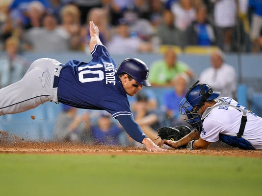 San Diego Padres' Hunter Renfroe, left, reaches for the base after being tagged out by Los Angeles Dodgers catcher Austin Barnes while trying to score on a single by Cory Spangenberg during the third inning of a baseball game Friday, Aug. 11, 2017, in Los Angeles. (AP Photo/Mark J. Terrill)