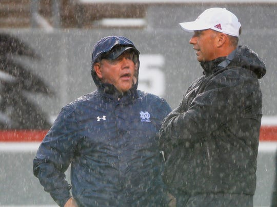 Fighting Irish coach Brian Kelly (left) chats with N.C. State's Dave Doeren prior to the game as Hurricane Matthew hit North Carolina.