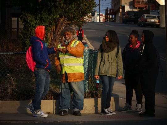 (left)12 year-old Nia-Gere Wright, a seventh grader, gets his morning fist bump from Earl Tate, 66, a volunteer crossing guard in northeast Wilmington.