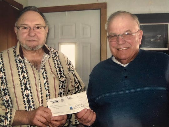 Don Osmunson and Gerald Neuser hold a check from the