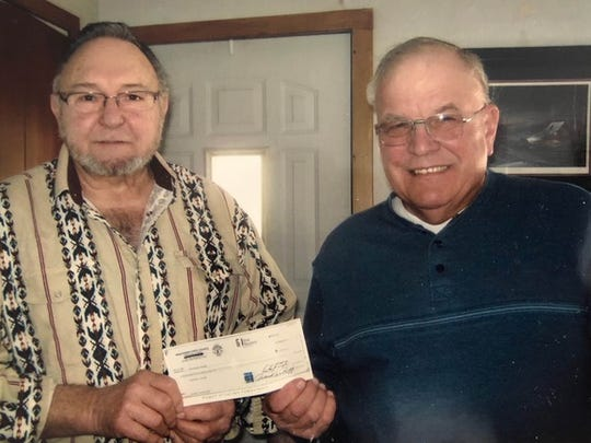 Don Osmunson and Gerald Neuser hold a check from the Knights of Columbus State Charity Fund.