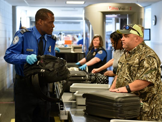 A transportation security officer removes a bag for