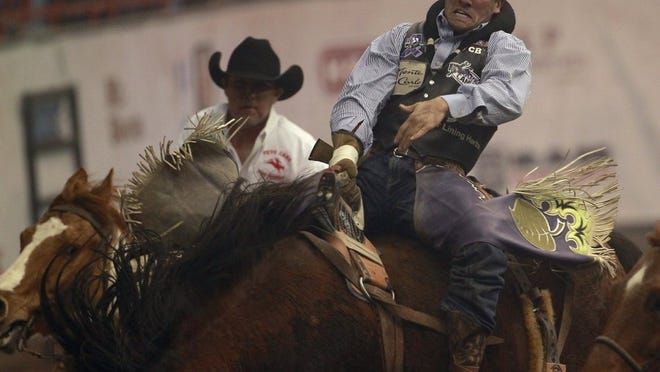Pick-up men try to help Caleb Bennett off Dirty Jacket, a Pete Carr Pro Rodeo horse, after his bareback ride at the 2017 San Angelo Rodeo.