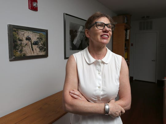 Artist Melinda Hunt at her Peekskill studio July 9, 2015. She has chronicled NYC's potter's field cemetery, Hart Island, in the Long Island Sound near City Island. A photograph behind her shows an open plot on the island.