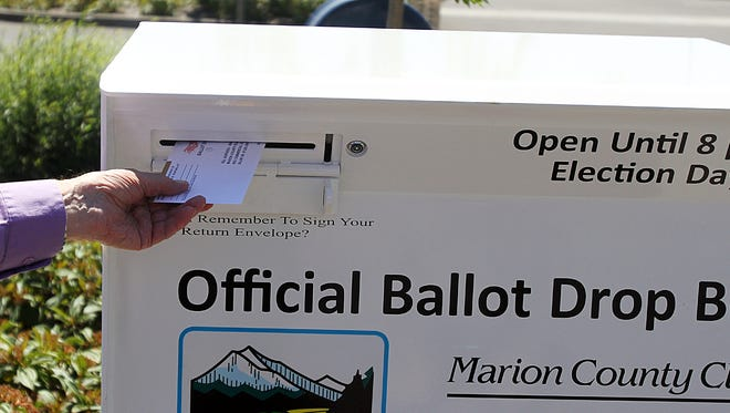 A man drops off his ballot in the first 24-hour ballot drop box in Marion County at Keizer Civic Center last year.