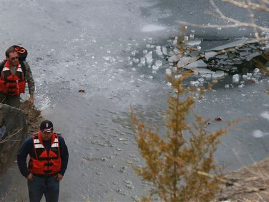 Rescue workers look for two juveniles who fell through the ice at a quarry Sunday, Jan. 18, 2015, in Spencer, Ind.