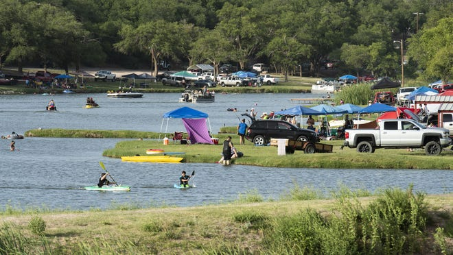 People celebrating the Fourth of July gather along the shore of Buffalo Springs Lake to play in the water and cook before the fireworks display on Friday, July 3, 2020, in Buffalo Springs, Texas.