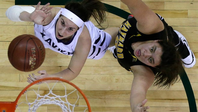 Xavier's Rachel Siciliano (left) puts up a shot against Hayward's Katie Taylor during Friday's WIAA Division 3 girls' state basketball semifinal basketball game at the Resch Center in Ashwaubenon.