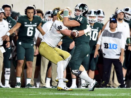 Brad Salem, far right, takes over as offensive coordinator as Michigan State tries to get Brian Lewerke (14) and the Spartans offense moving again in 2019.