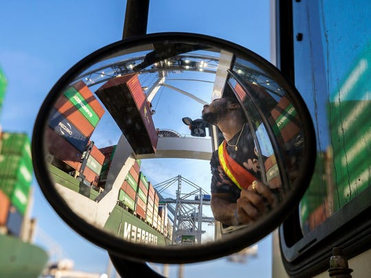 In this June, 19, 2018 photo, a jockey truck driver waits for his load of a shipping container to clear his trailer as a shore crane lifts the 40-foot onto the container vessel Ever Linking at the Port of Savannah in Savannah, Ga. The U.S. has threatened to impose 25 percent duties on $34 billion in Chinese products starting Friday, July 6, and China has said it will fire back with corresponding tariffs.