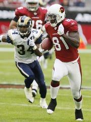 Cardinals receiver Anquan Boldin runs past Rams defender