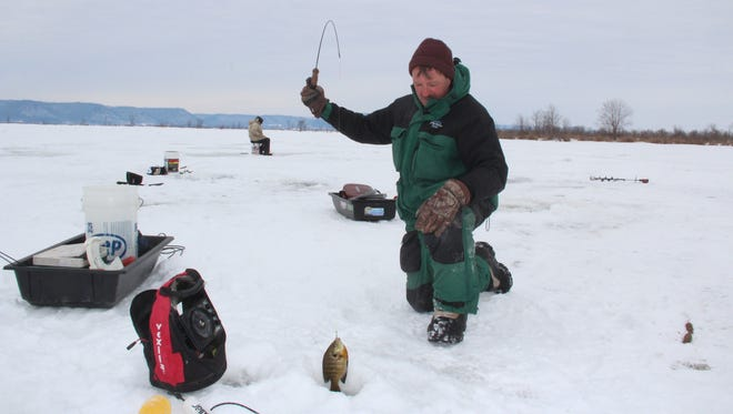 Frank Ouimet of Ferryville, Wis. lands a bluegill while ice fishing on the Mississippi River near Stoddard, Wis. Ouimet and Mike Gorman of Salem, Wis. (background) would have preferred to fish within a few miles of Ferryville but drove about 20 miles to Stoddard to avoid a trespassing ticket. A 2005 state law made it illegal for pedestrians to bisect railroad tracks except at established crossings.