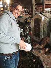 Gina Atsma of Amity, the Polk County Dairy Princess-Ambassador and new State First Alternate, feeds Jersey calves as part of her chores at her family's Atsma Dairy in Amity.