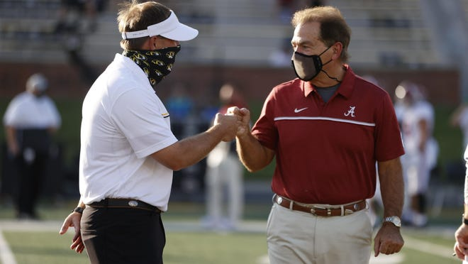 Missouri head coach Eli Drinkwitz bumps fists with Alabama head coach Nick Saban before a Southeastern Conference game Saturday at Faurot Field.