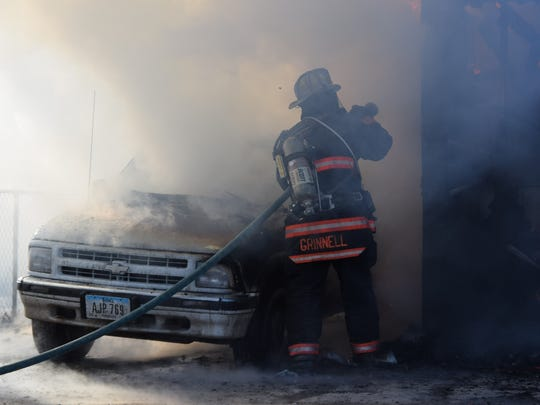 A Grinnell fire fighter goes after the remains of a fire that destroyed a garage and the vehicle next to it at 500 6 Ave., Grinnell on Sunday, Feb. 12.