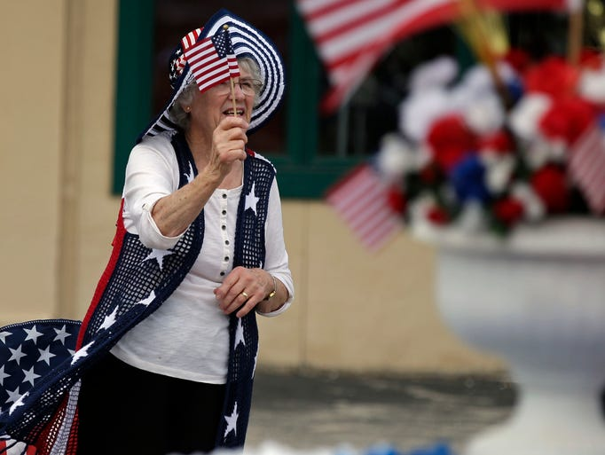 Gladys Javes waves her flag as a float passes during
