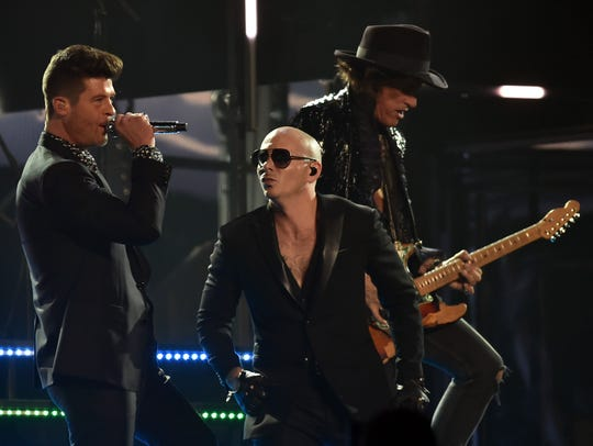 Pitbull (center) performs with Joe Perry (right) and