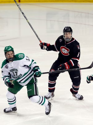 UND's Colten St. Clair and St. Cloud State's Daniel Tedesco move to a loose puck on Friday at the Ralph Engelstad Arena in Grand Forks, N.D.