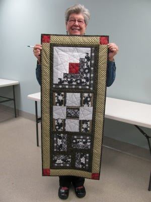 Vicki Kauth with sample of a class table runner.